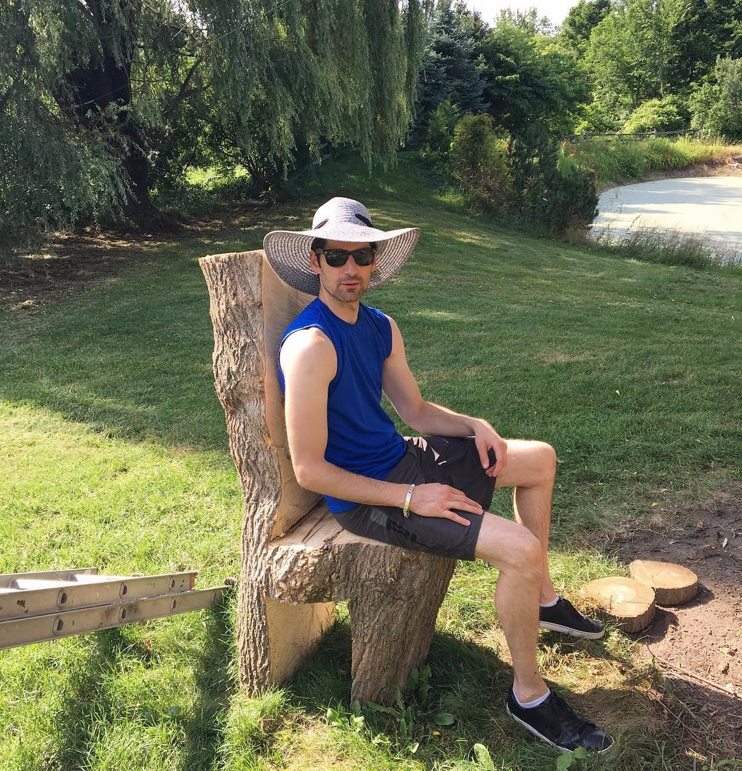 Ben Aaron is wearing a sleeveless blue T-shirt and black half-pant. He is wearing a hat and sunglasses. He is sitting on a tree chair.
