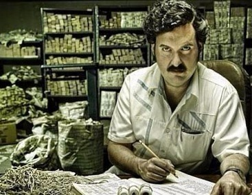 Pablo Escobar is writing and is looking at the camera. He ha a mustache.