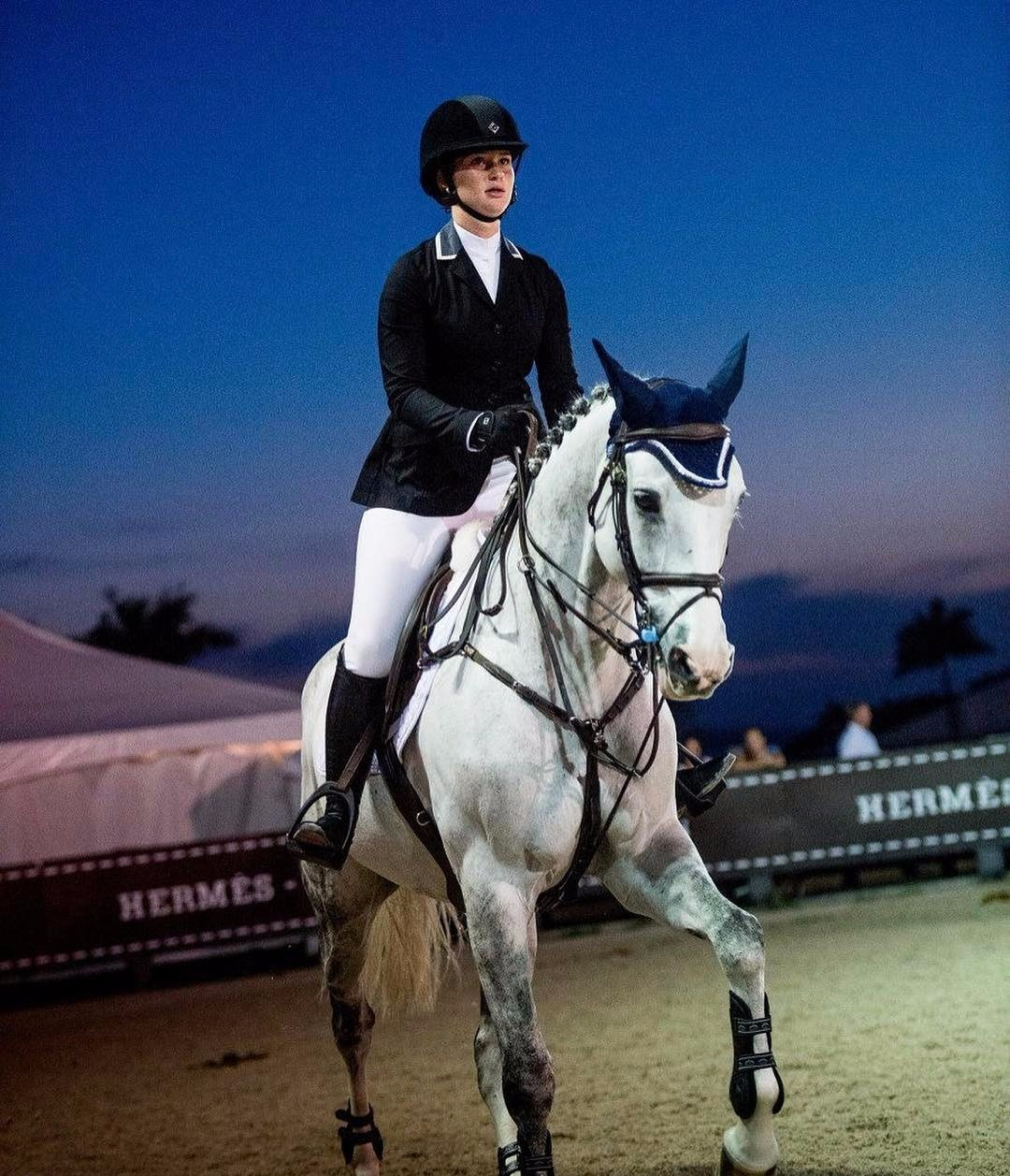 Jennifer Katherine Gate riding on a white horse. She looks confident while she is riding. She is dressed in a professional horse riding suit.