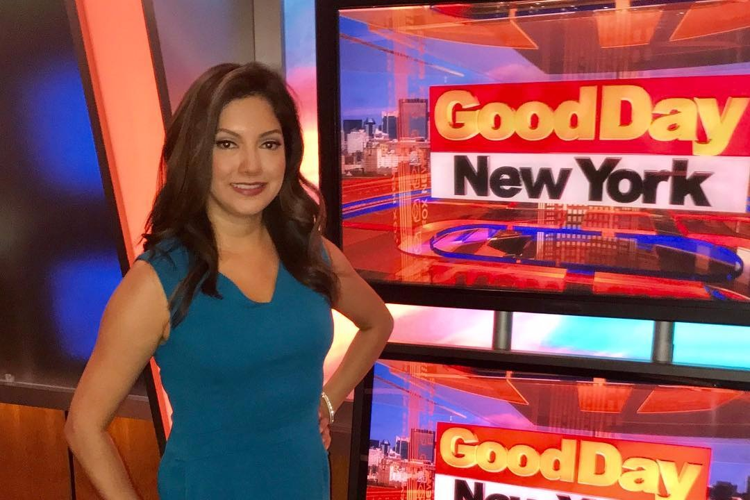 Ines Rosales in the Good Day New York studio standing in front of two monitors that say Good Day New York