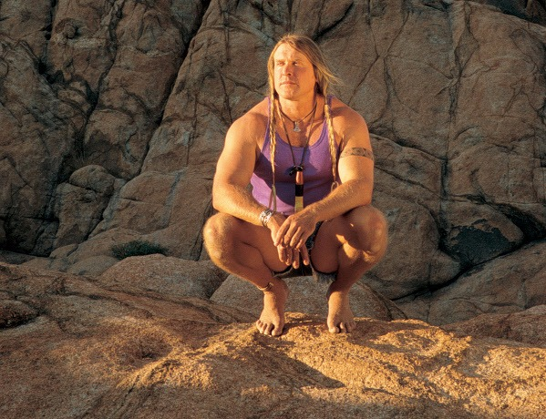 Cody Lundin is sitting on a huge rock. He has long braided hair.