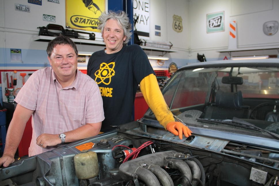 Mike Brewer and Edd China are standing beside a car. They are smiling at the camera.