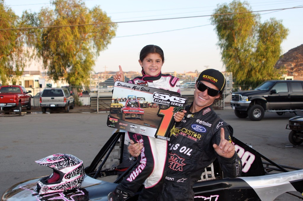 Brian Deegan carrying his daughter Brian in his arms. They are both smiling with joy as Hailie has secured the first position in a motocross competition. They are both in their sports dress.