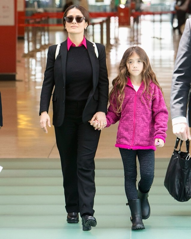 Salma Hayek and Valentina Paloma Pinault are walking hands on hand. Salma is wearing is formal like black sweater and pants and Valentina is wearing pink jacket and black trousers in black boot.