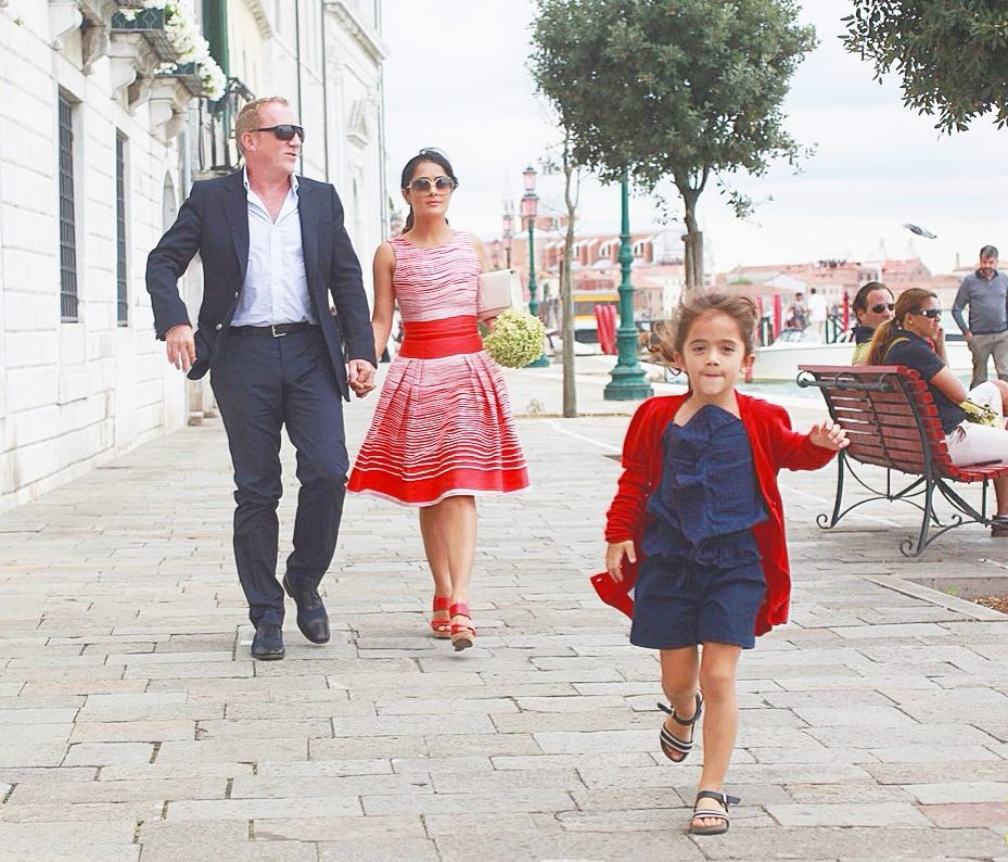 Valentina Paloma Pinault and her parents are walking down a street. Valentina is rushing forward whereas her parents walk romantically behind her.
