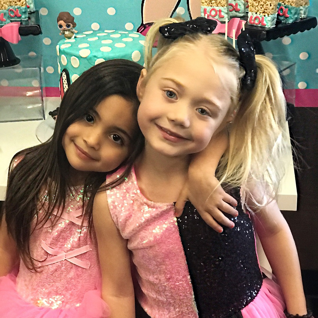Everleigh Soutas and her bestfriend Ava Foley are smiling at the camera. Both of them are wearing pink dress.