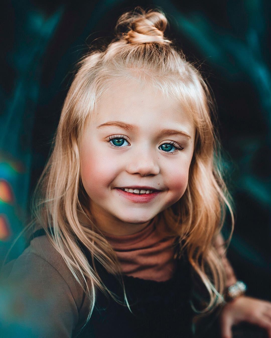 Everleigh Soutas has a small bun on her head. She has blonde hair and blue eyes. She is very cute.