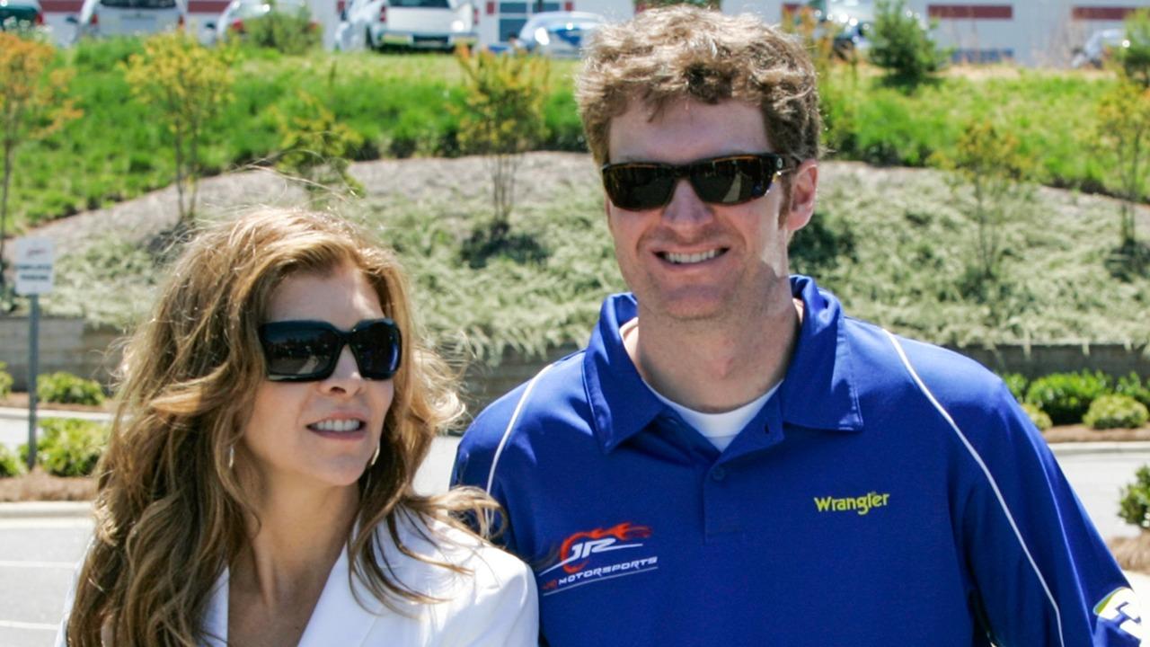 Teresa Earnhardt and her son Dale Earnhardt Jr. are wearing black sunglasses. Dale Jr. is wearing a blue t-shirt.