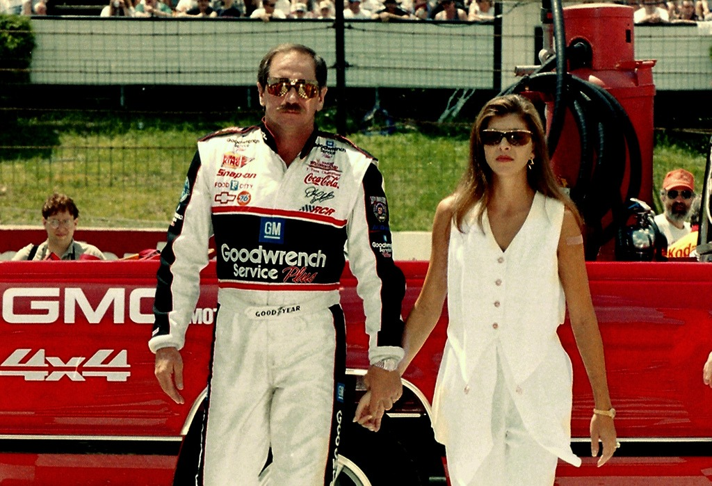 Dale Earnhardt and Teresa Earnhardt are holding hands on the picture. There is a racer car behind them.