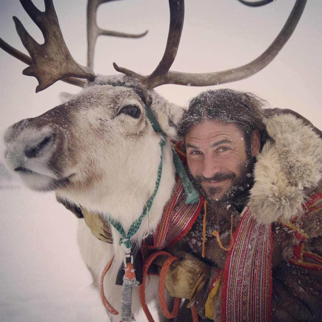 Hazen Audel is hugging a reindeer in a snowy path.
