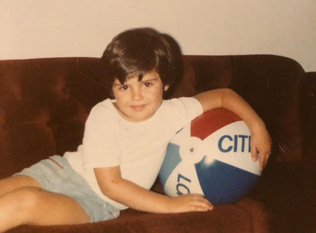 A young Gary Vaynerchuk leaning on a beach ball