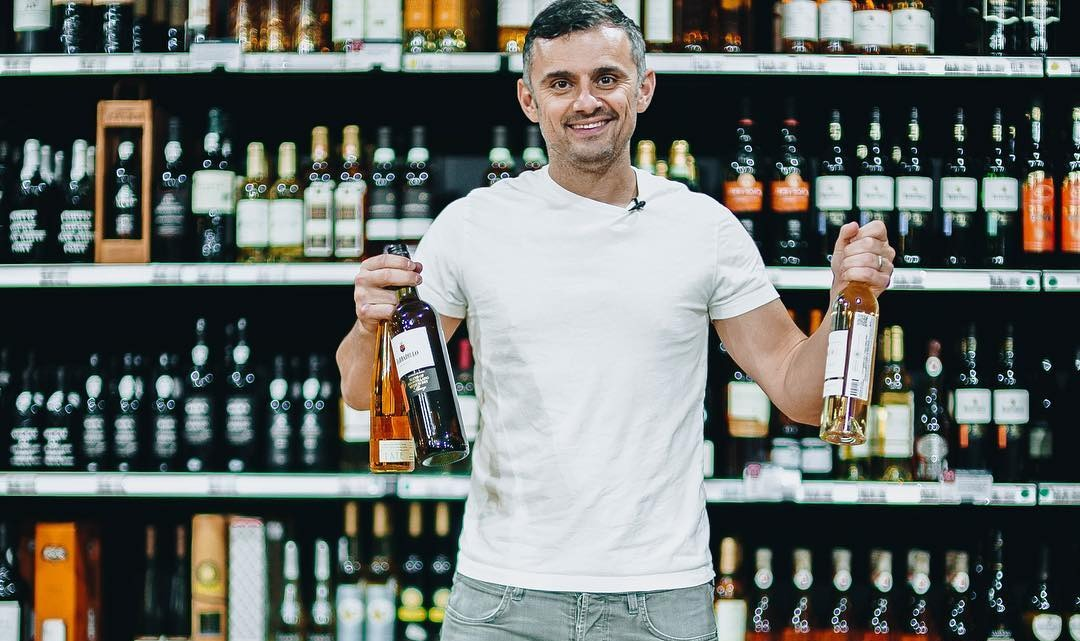 Gary Vaynerchuk holding two bottles of wine in each hand. there's are wine bottles in racks behind him