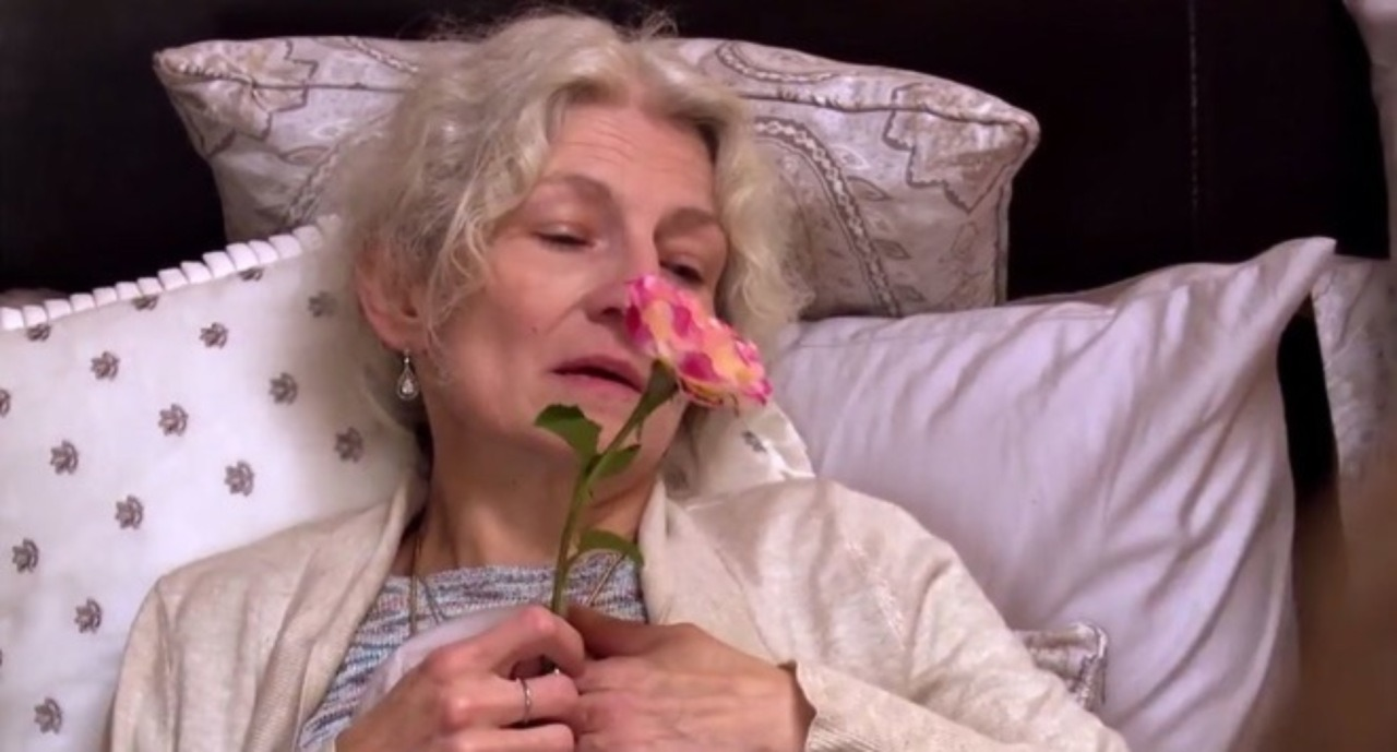 Ami Brown is holding a flower in her bed