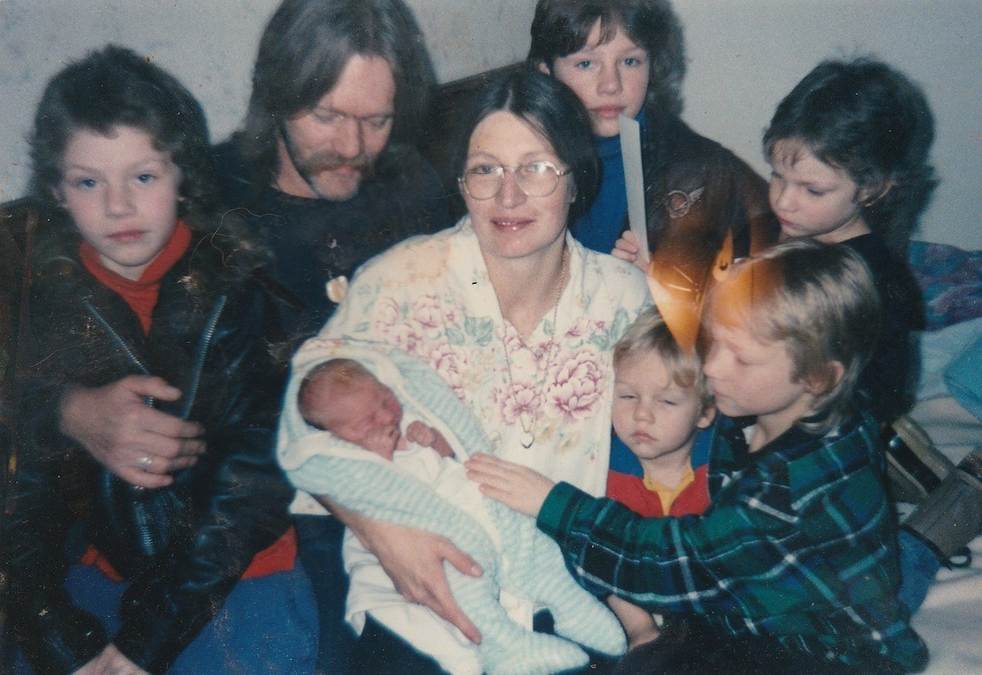 Ami Brown holding her youngest baby surrounded by her young children