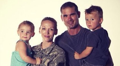 Addie Zinone standing with her husband in an US  military dress. She is carrying her daughter and her husband is carrying the son.