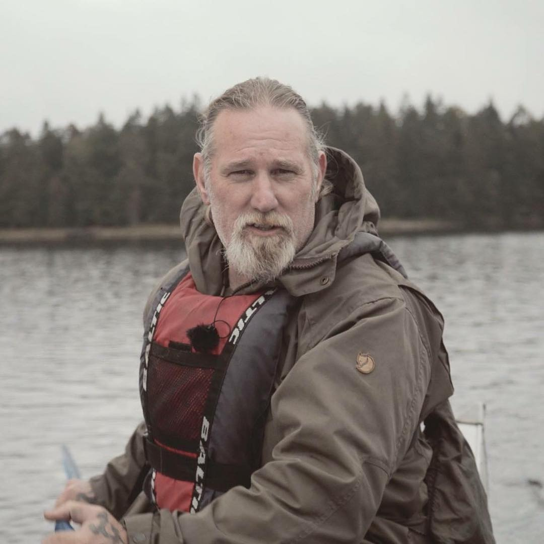 Dave Canterbury poses for the camera while he enjoys boating. He is peddling against the water wearing his life jacket.