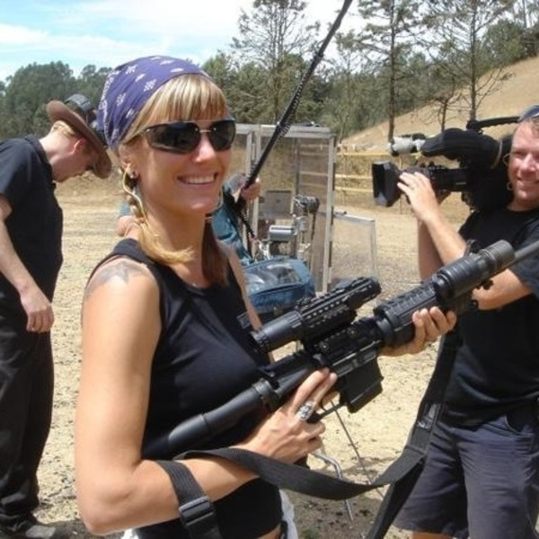 Scottie Chapanman is holding a heavy gun during her shoot. She is smiling an d is wearing a sleeveless black top and white pants.
