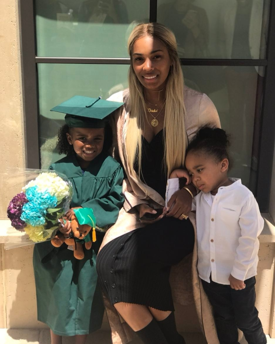 Dreka Gates is sitting with two children on her side. They are posing for at the camera.