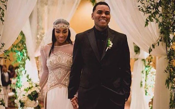 Dreka Gates is wearing a white gown and Kevin is wearing a black suit. They are holding hands.