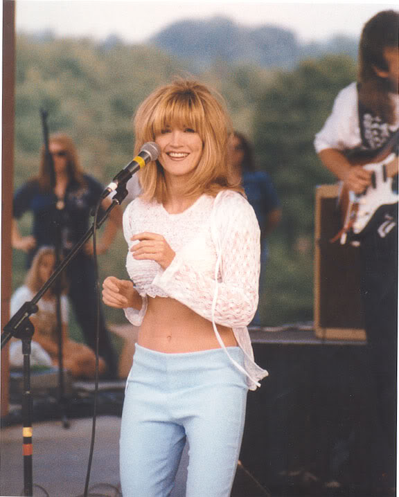 Crystal Bernard is standing, singing on a mic. She is wearing blue jeans and white crop-top.