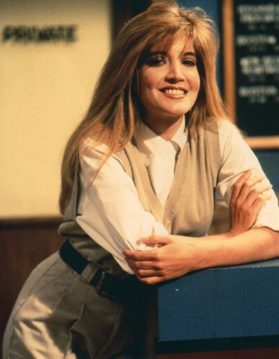 Crytal Bernard portraying the role of Helen Chappell in television sitcom Wings. She is leaning on to a table in front of her and is smiling.