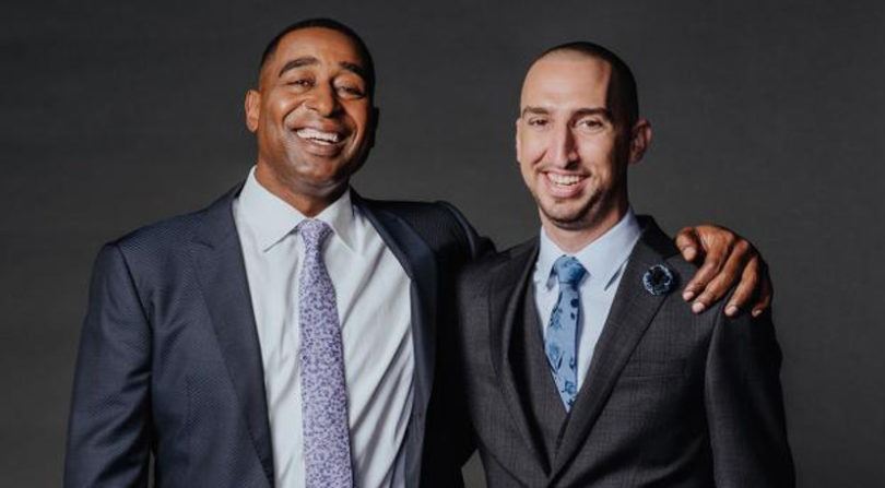 Nick Wright and Cris Carter are smiling at the camera. Cris is hugging Nick.