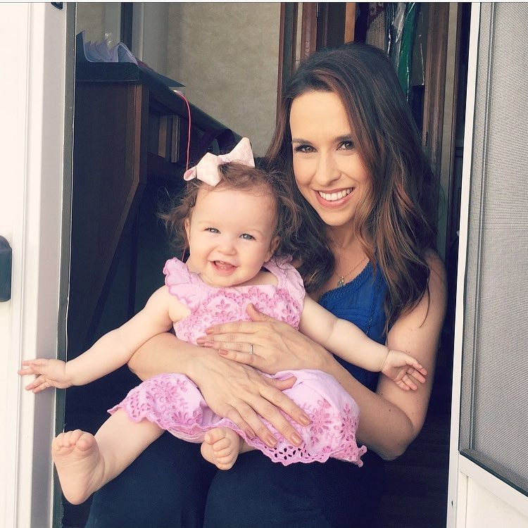 Lacey Chabert is carrying her daughter. Her daughter is wearing a pink dress.