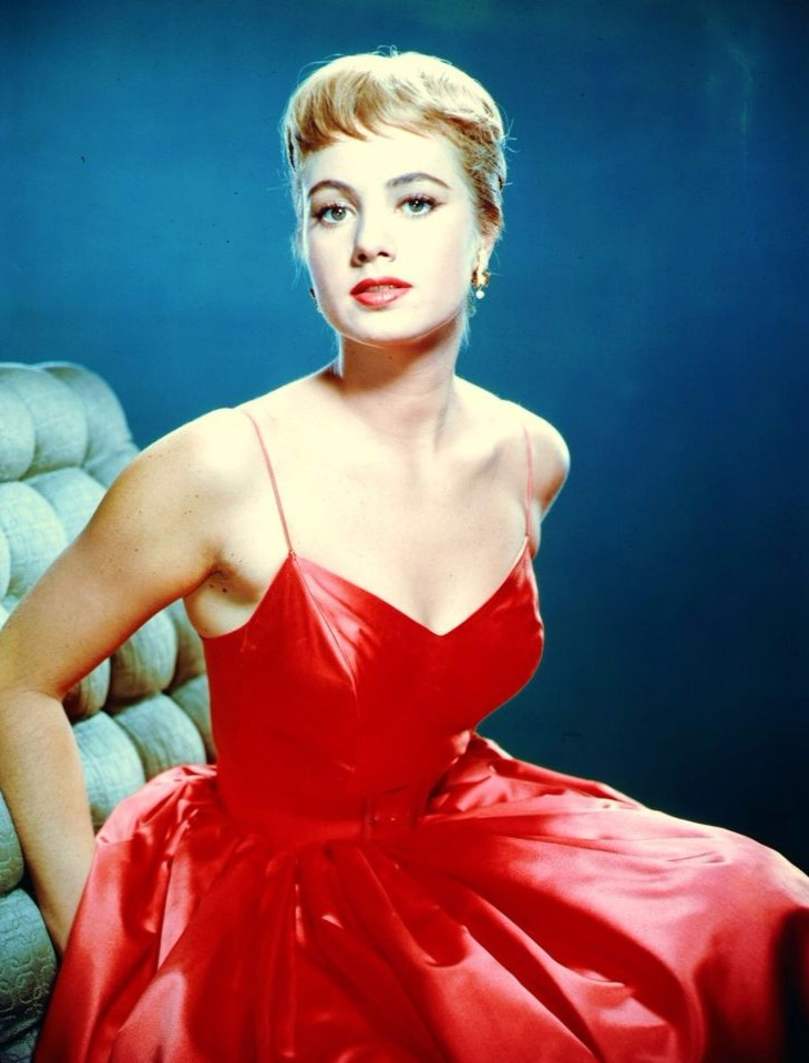 Shirley Jones is wearing a beautiful red dress, sitting on an upholstered chair.