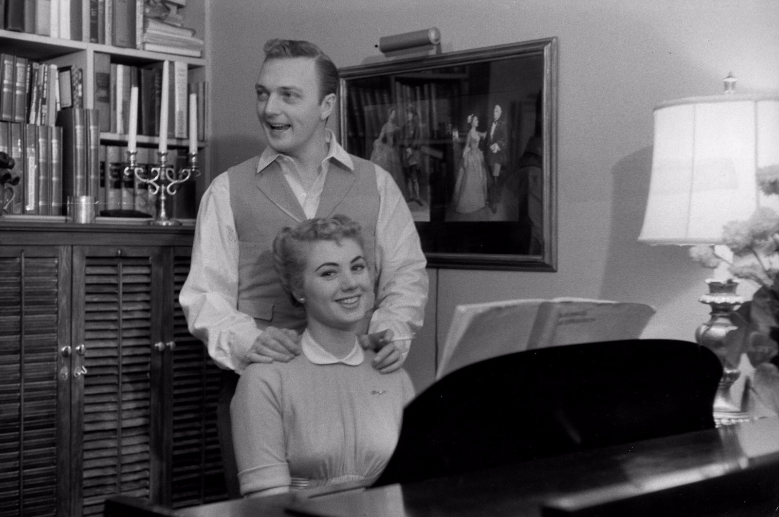 Jack Cassidy is standing behind a chair on which his wife Shirley Jones is sitting. Jack is looking away from the camera.