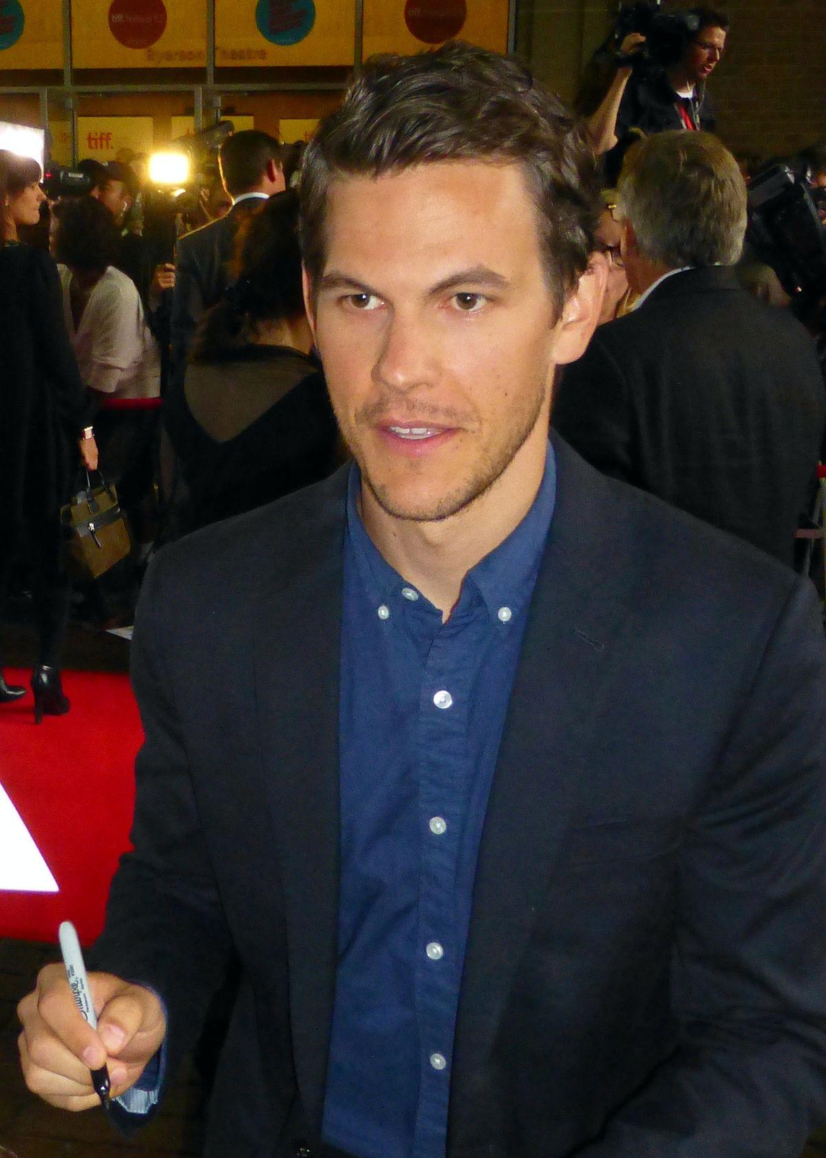 Tom Lipinski is wearing a blue shirt followed by suit