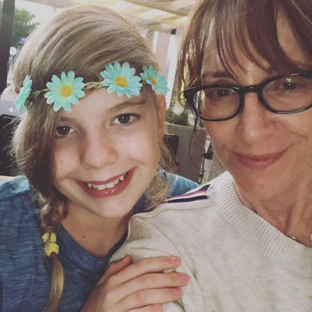 Katey Sagal in white t shirt and her daughter Esme in blue t shirt with a flower headband.