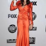 Katey Sagal in wearing an orange dress and carrying a golden globe award.