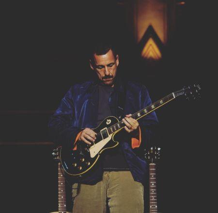 Adam Sandler playing guitar