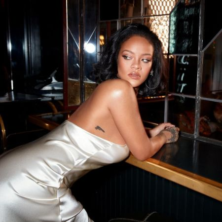 Rihanna posing for picture in a sexy dress