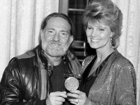 Connie Koepke and her husband Willie Nelson holding a medal.