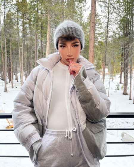 James Charles taking a picture at a resort covered with snow