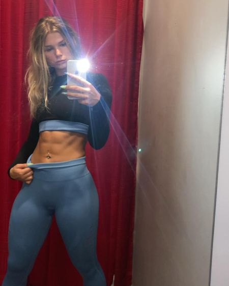 Taylor Kamphorst taking a mirror selfie and flexing her abs