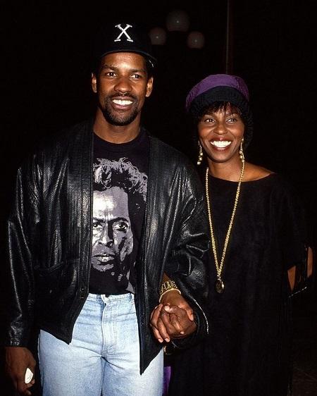 Pauletta Pearson holding the hand of her husband Denzel Washington