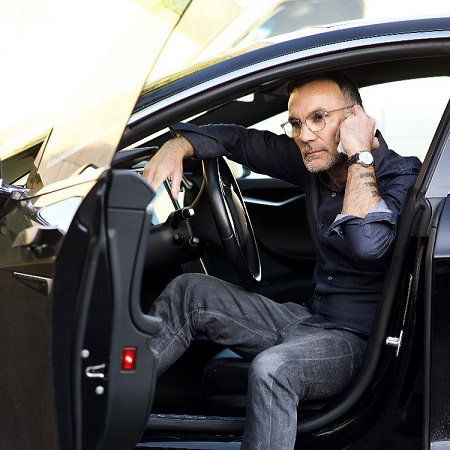 Jonathan Antin husband of Sescie Antin posing on his car