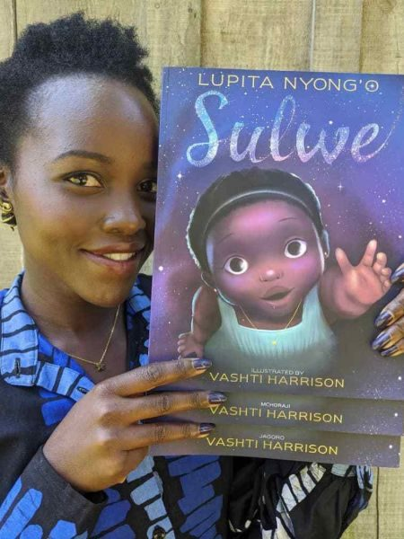 Lupita Nyong'o holding her book Sulwe