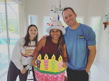 Mika Kleinschmidt posing on her birthday with her husband and daughter