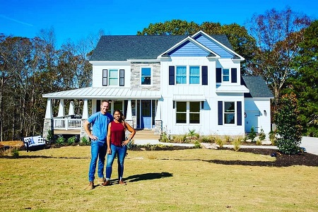 Mika McGhee and her husband Brain posing behind their house