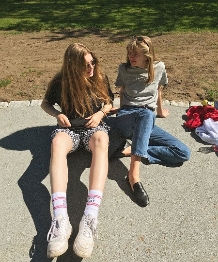 Girl in Red  spending her time with her sister in a park