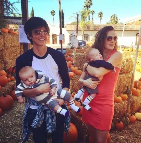 Stephanie Allynne and Tig Notaro holding their sons in their arms